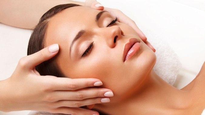 Femme maquillé et qui a une peau net qui reçoit un massage du visage